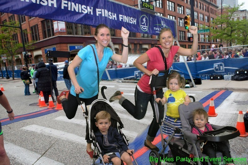 two moms running while pushing strollers with cute kids acros the finish Line  at 2014 Fifth Third River Bank Run in Grand Rapids MI