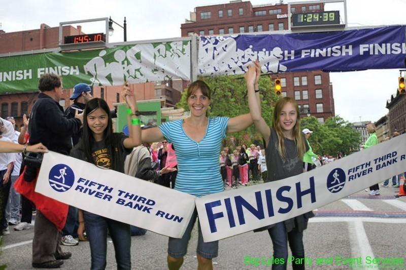 three girls giving high five holding finish line sign  at 2014 Fifth Third River Bank Run in Grand Rapids MI