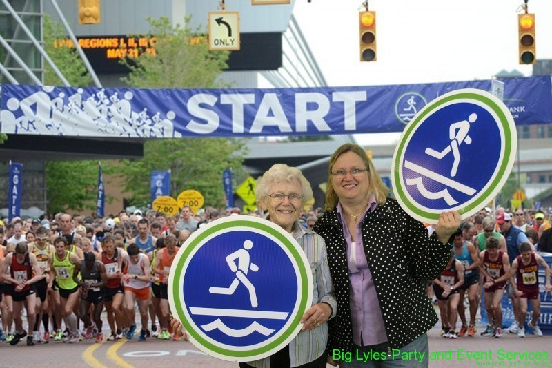 Young and Old woman  at the staring ling holding sign  at 2014 Fifth Third River Bank Run in Grand Rapids MI