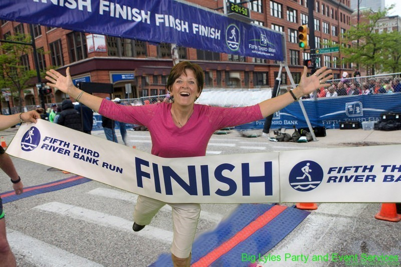 Happy lady running across the finish line  at 2014 Fifth Third River Bank Run in Grand Rapids MI