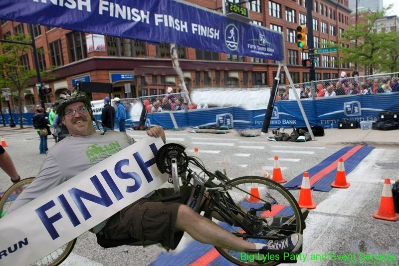 Marathon participant on bike at finish line  at 2014 Fifth Third River Bank Run in Grand Rapids MI