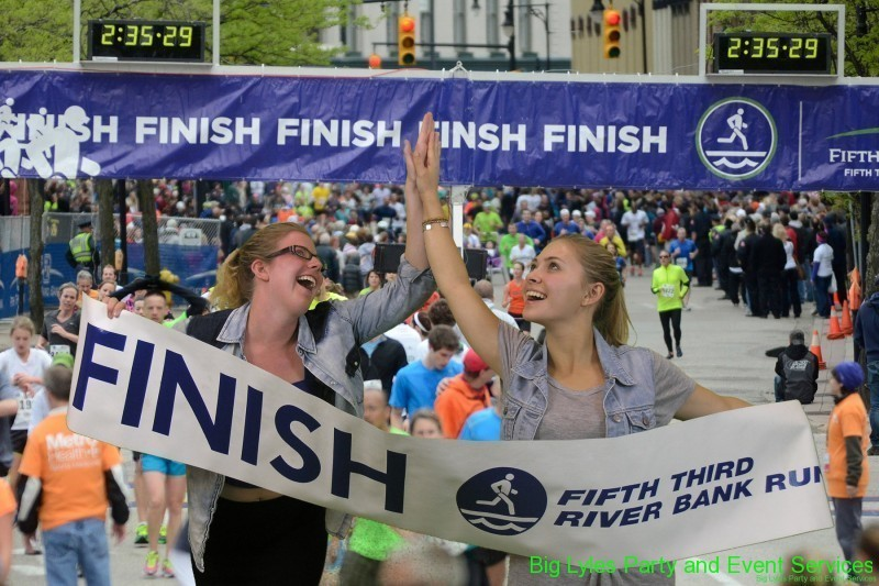 two girls giving high five running across finish line  at 2014 Fifth Third River Bank Run in Grand Rapids MI
