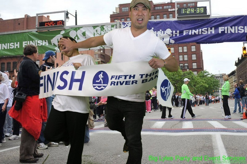 man pushing woman as they cross finish line  at 2014 Fifth Third River Bank Run in Grand Rapids MI