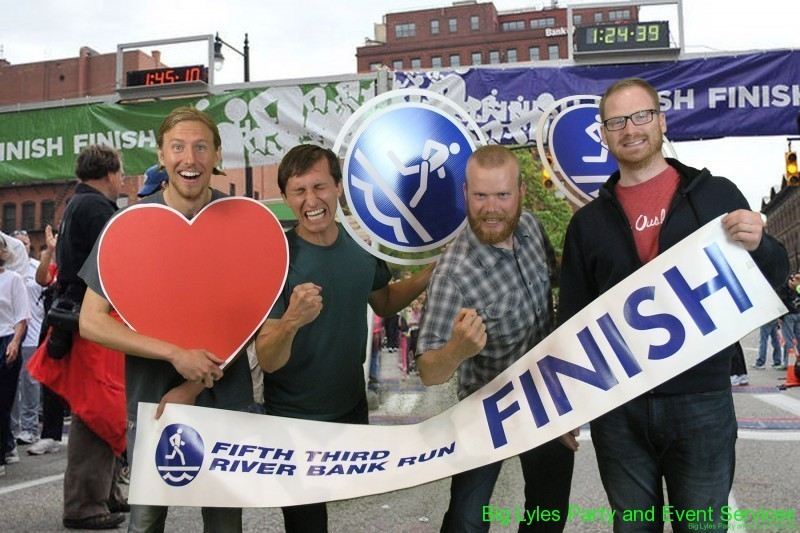 four guys with a heart sign making funny faces running across finish line  at 2014 Fifth Third River Bank Run in Grand Rapids MI