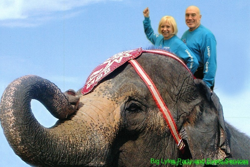 Couple riding an elephant at green screen photo event