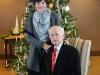 Two people in front of the Christmas tree.