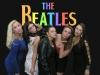 Girls pose in front of Beatles logo.