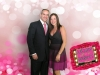 Couple poses together in front of beautiful pink background.